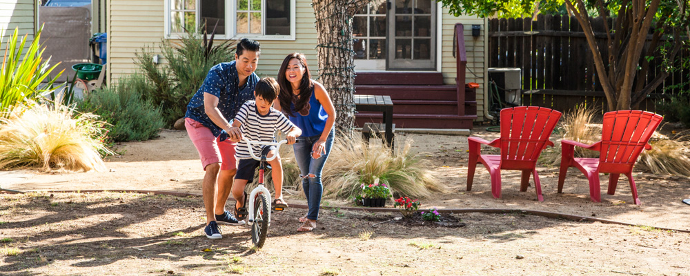 Mom and Dad teaching son to ride a bike.