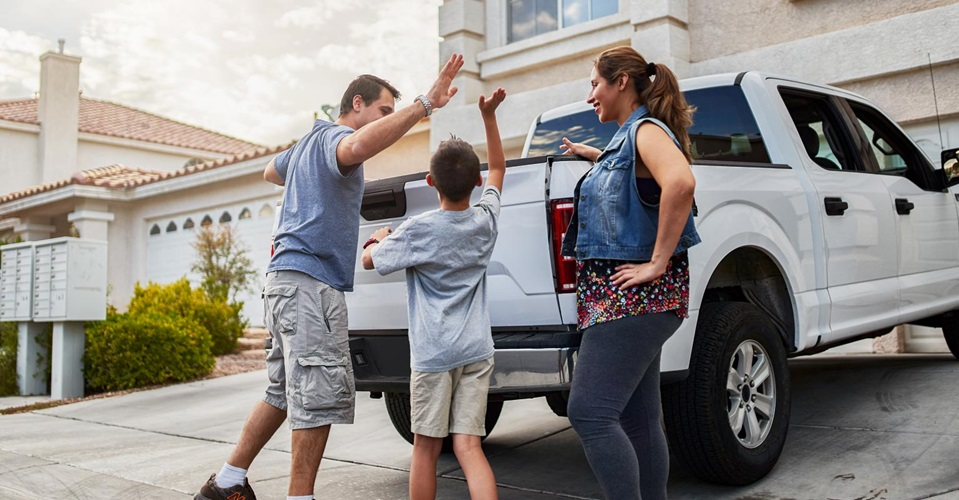 Son high-fiving father next to white truck