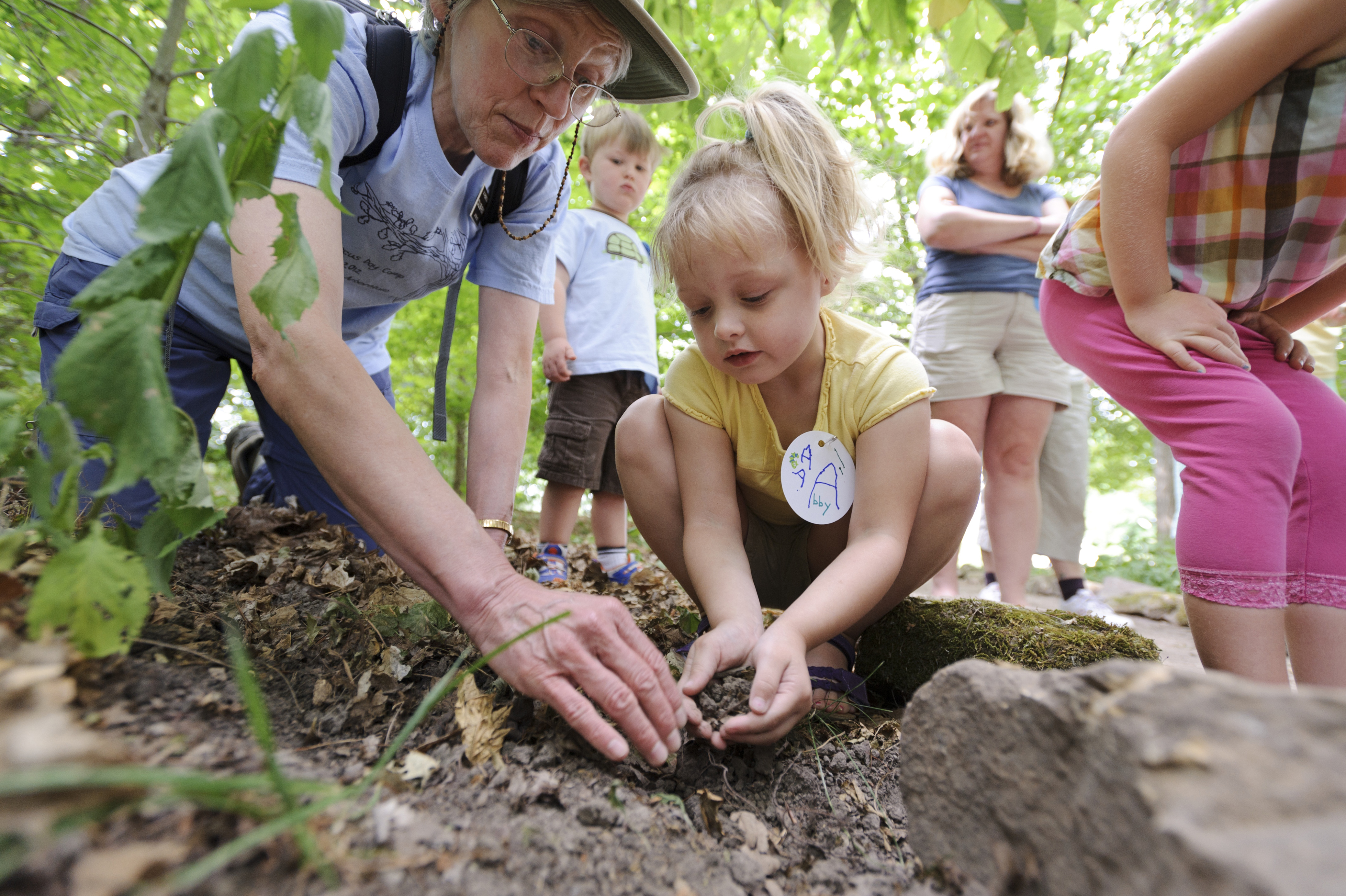 Lady helping a little girl plant a tree