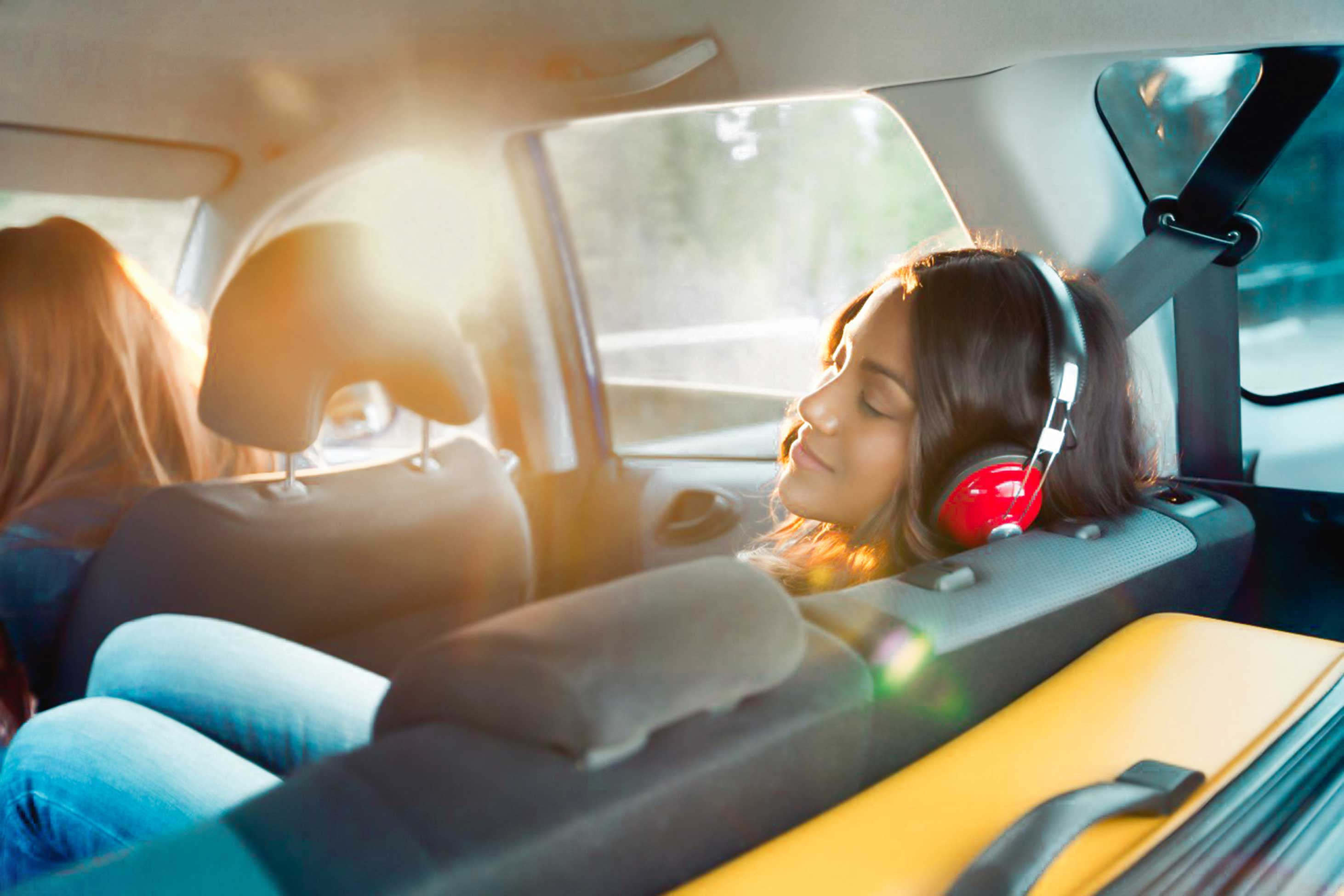 Woman listening to headphones in car