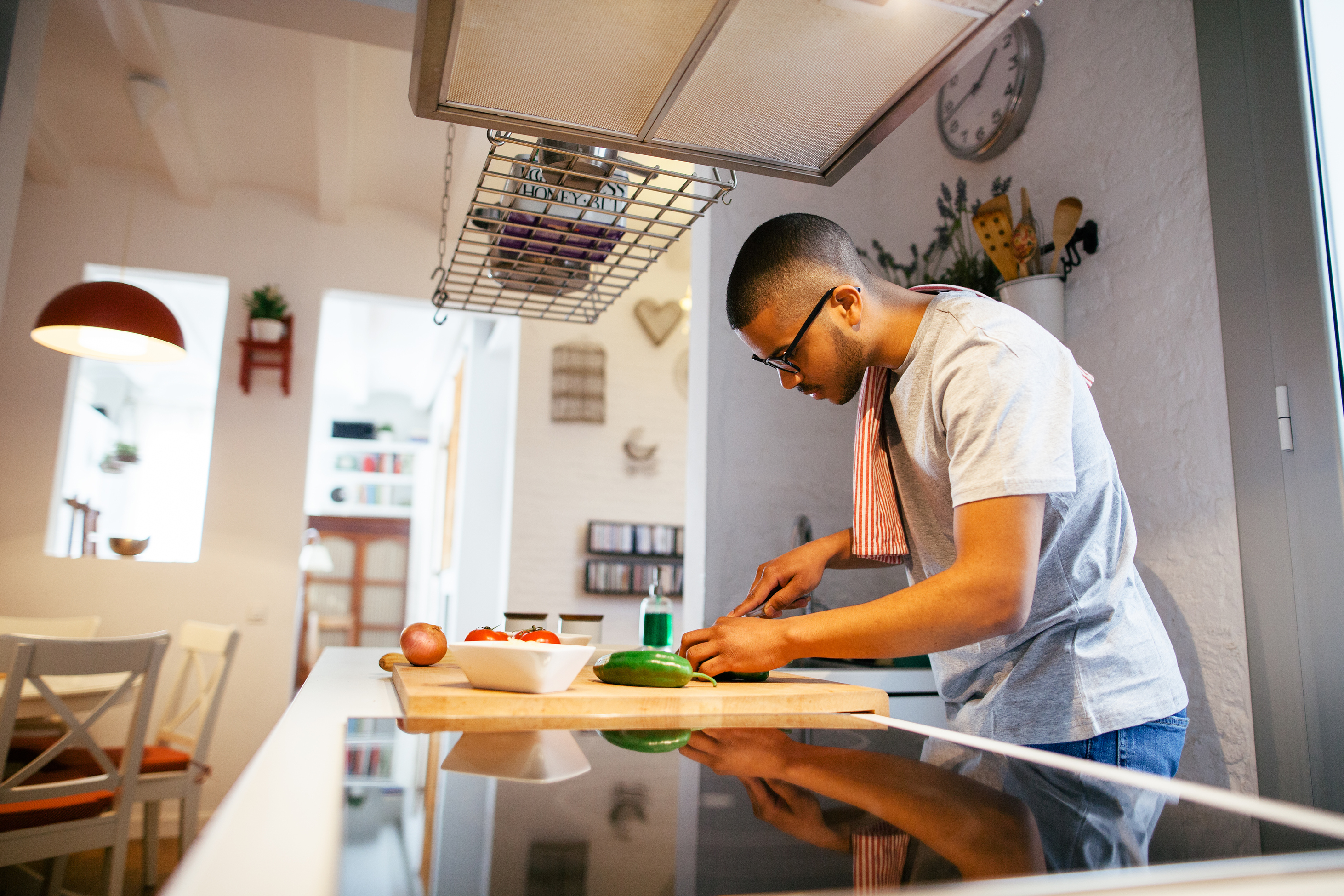 Black man cutting food in his kitchen