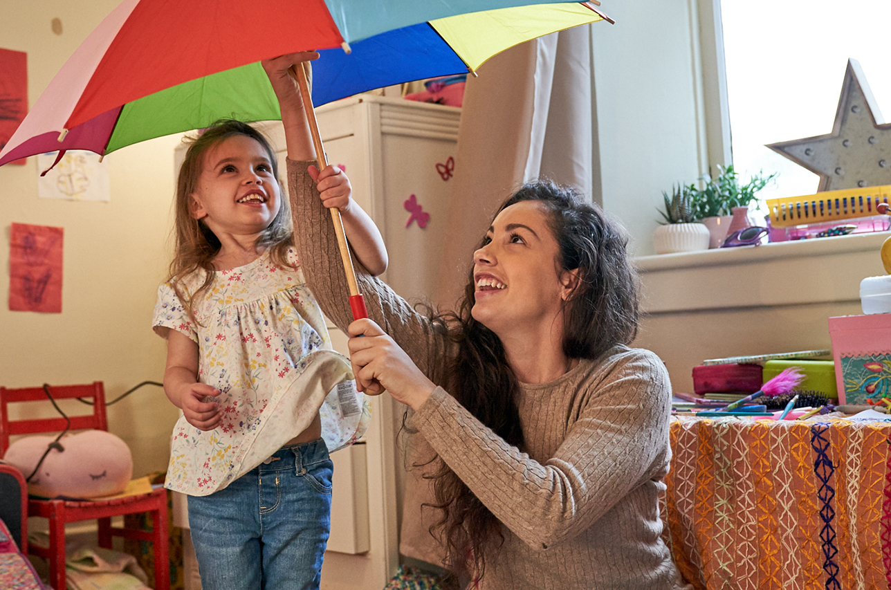 Mother opening an umbrella for her daughter