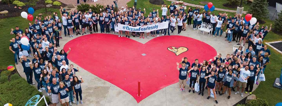 several people surrounding large heart painted on ground